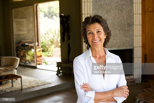 woman standing with arms crossed smiling in modern home - 60 64 years stock pictures, royalty-free photos & images