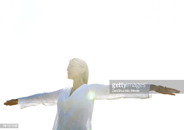 Woman standing with arms out, low angle view, backlit