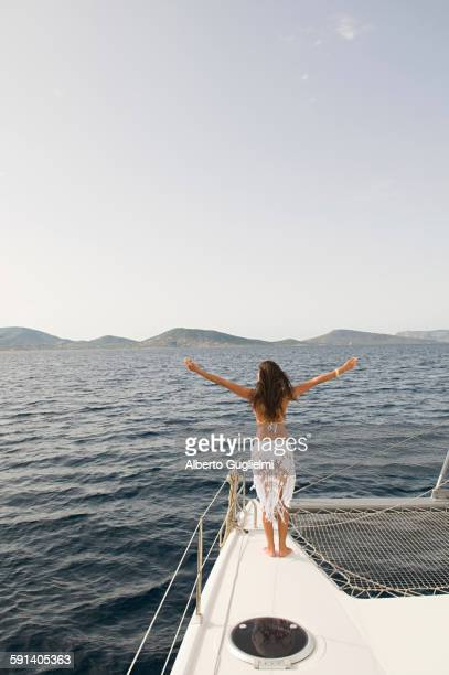 Woman standing with arms outstretched on sailboat deck