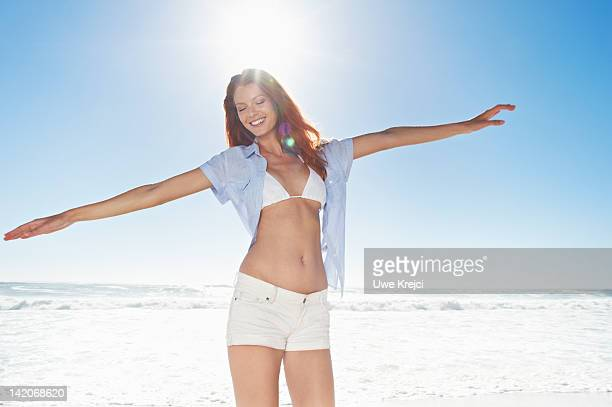 woman standing with arms outstretched - helemaal losgeknoopt stockfoto's en -beelden