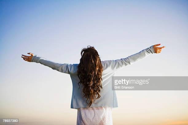 woman standing with arms outstretched. - les bras écartés photos et images de collection