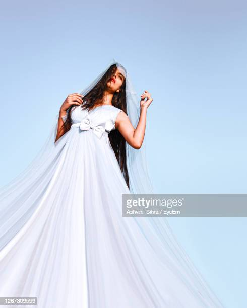 woman standing with arms raised against blue sky - evening gown stock pictures, royalty-free photos & images