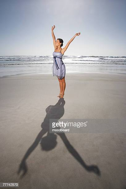 woman standing with arms raised on the beach - cocktail dress stock pictures, royalty-free photos & images