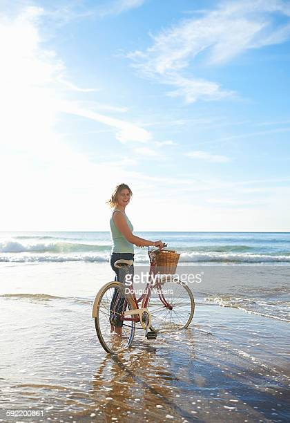 Woman standing with bicycle at beach.