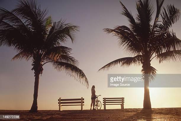 Frau stehend mit Fahrrad von Palmen