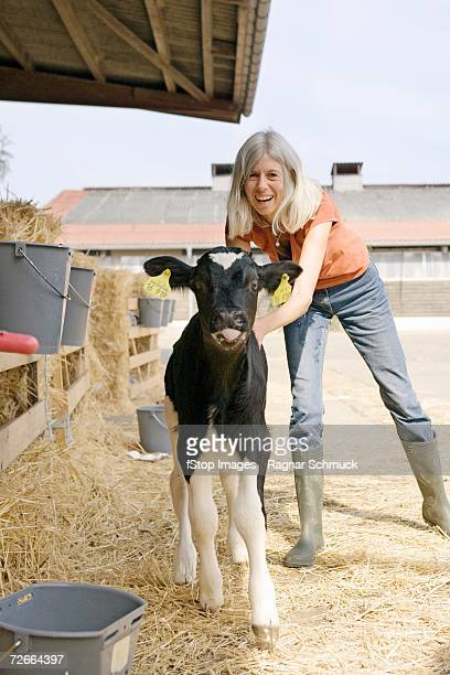 Woman standing with calf in farmyard