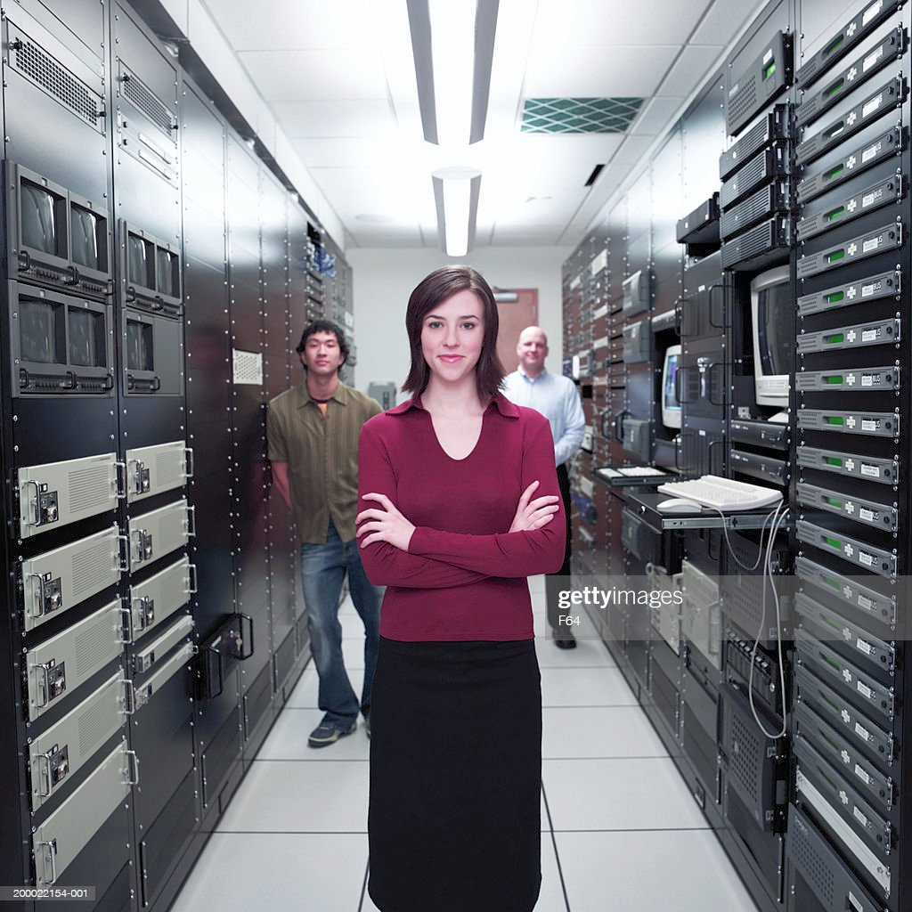 Woman standing with coworkers in server room (selective focus) : Stock Photo