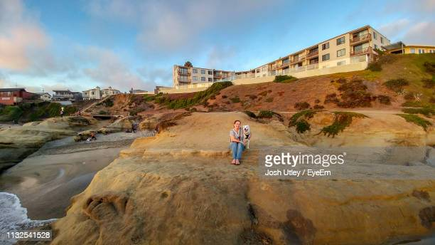 Woman Standing With Dog On Rocky Shore Against Sky During Sunset
