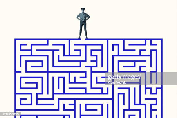 woman standing with hand on hip over blue maze - decisions stock pictures, royalty-free photos & images