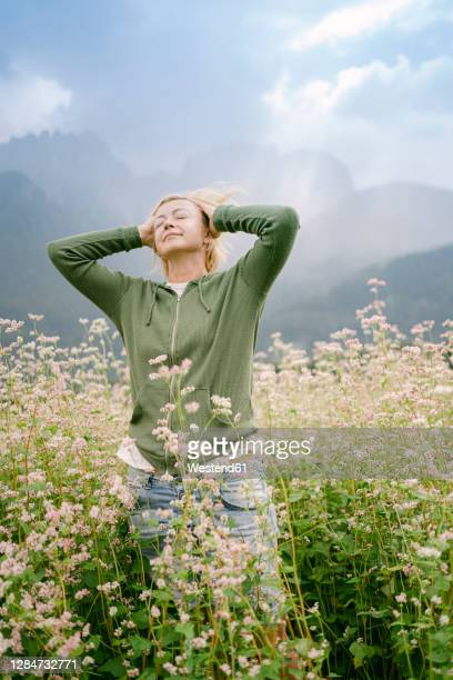 woman standing with hands behind head amidst plants on field - three quarter length stock pictures, royalty-free photos & images