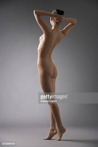 Woman standing with hands behind head