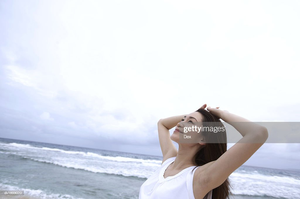 Woman Standing With Her Arms Behind Her Head on a Beach : Stock Photo