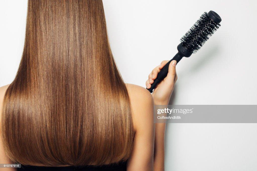 Mulher em pé com ela de volta e demonstra penteado luxuoso : Foto de stock