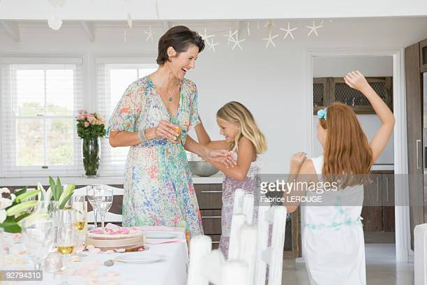 Woman standing with her daughters playing at a dining table
