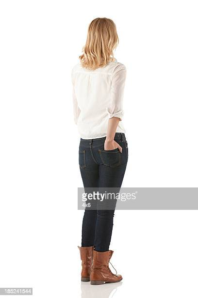woman standing with her hands in pockets - staan stockfoto's en -beelden