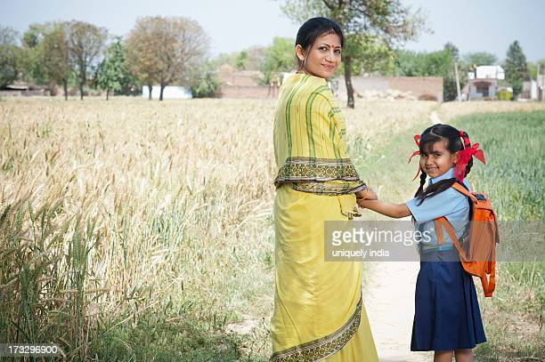 Woman standing with her schoolgirl in the field, Sohna, Haryana, India