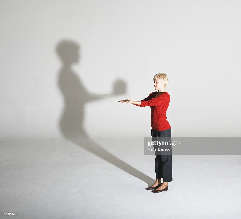Woman standing with her shadow giving her a gift : Stock Photo