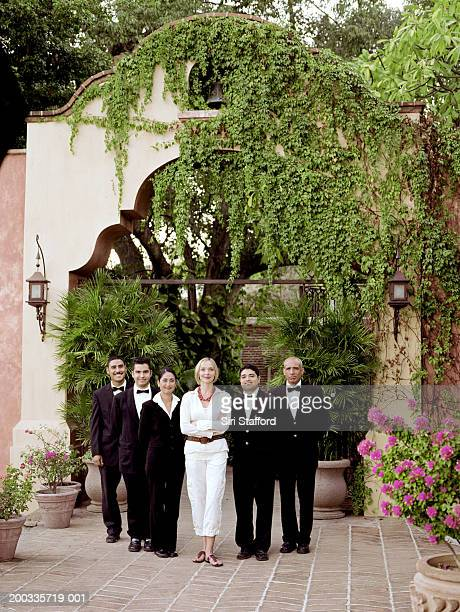 Woman standing with hotel staff, portrait