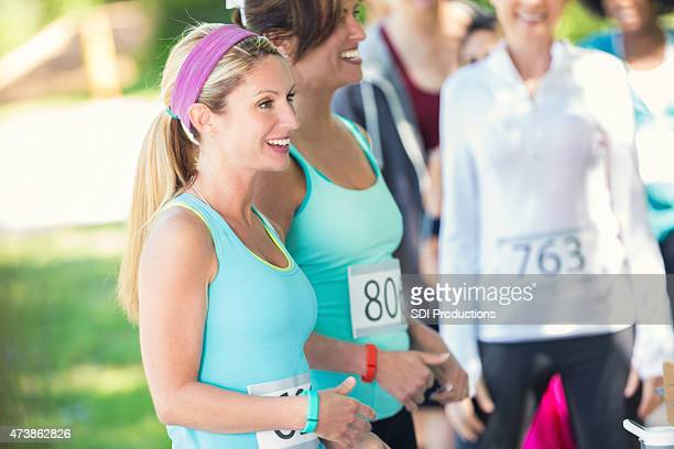 Woman standing with other runners after marathon or race