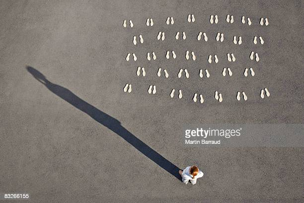 Woman standing with pairs of footprints