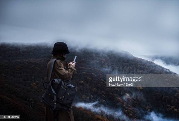 Woman Standing With Smart Phone Against Sky