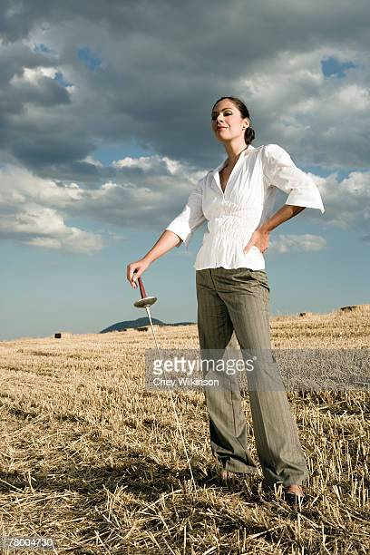 Woman standing with sword in wheat field.