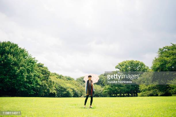 woman standing with umbrella - yusuke nishizawa stock pictures, royalty-free photos & images