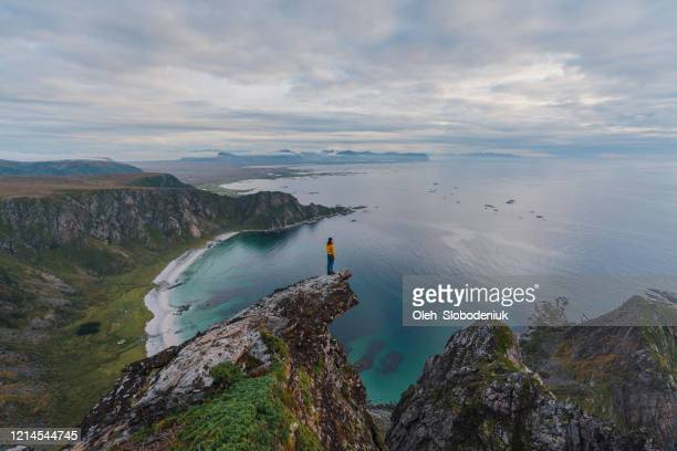 woman standing with view on beach on lofoten island - northern norway stock pictures, royalty-free photos & images