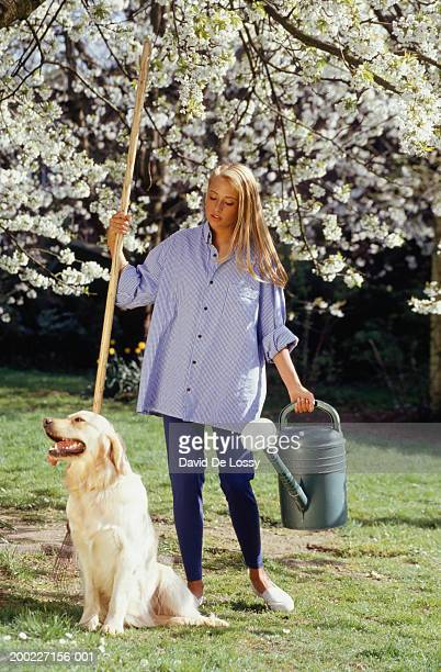 Woman standing with watering can in garden next to dog