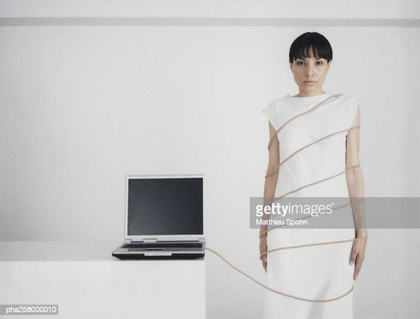 Woman standing wrapped in cord attached to laptop