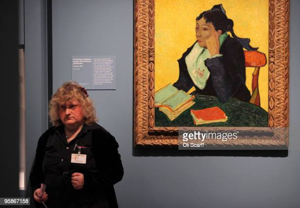A woman stands adjacent to an oil painting by acclaimed Dutch artist Vincent Van Gogh entitled 'Madame JosephMichel Ginoux with Books' in an...