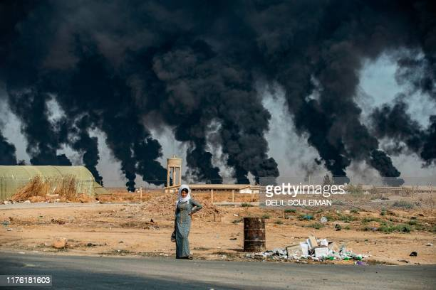 TOPSHOT A woman stands along the side of a road on the outskirts of the town of Tal Tamr near the Syrian Kurdish town of Ras alAin along the border...