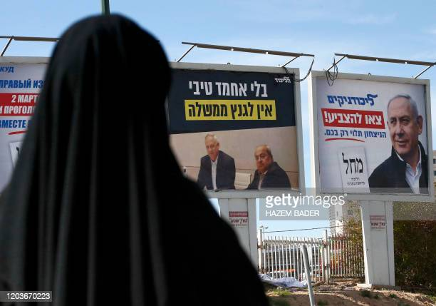 A woman stands along the side of a street in the southern Israeli city of Beersheba on February 27 looking at electoral billboards ahead of the...