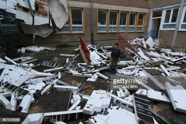 TOPSHOT A woman stands amid parts of the roof structure of a primary school lying in the schoolyard on January 19 2018 in Halberstadt eastern Germany...