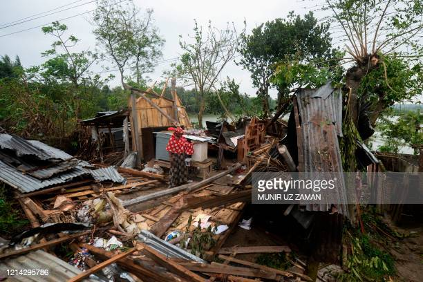 TOPSHOT A woman stands amidst the debris of her house damaged by cyclone Amphan in Satkhira on May 21 2020 The strongest cyclone in decades slammed...