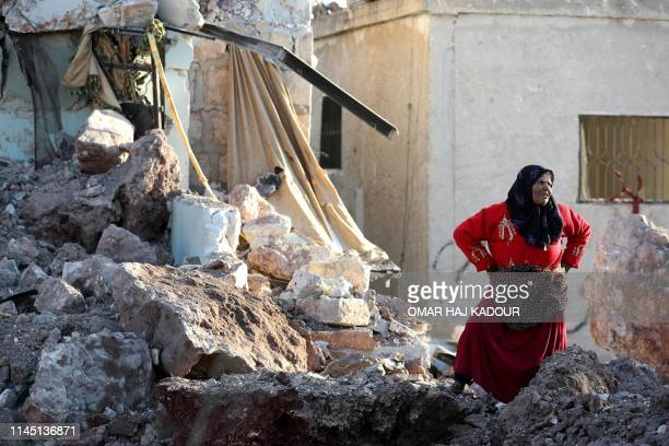 A woman stands amidst the rubble of a building that was reportedly destroyed during air strikes by the Syrian regime ally Russia in the town of...
