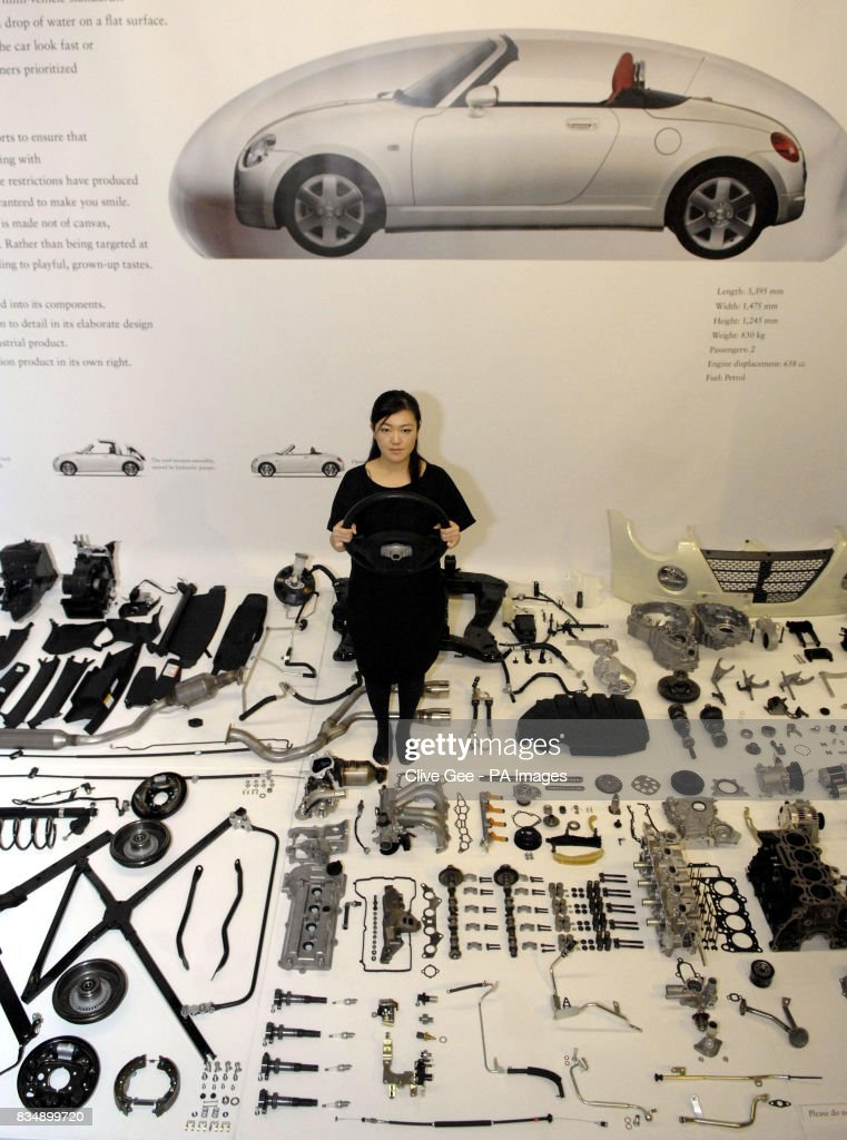 A woman stands among car parts of a Daihatsu Copen in the Science