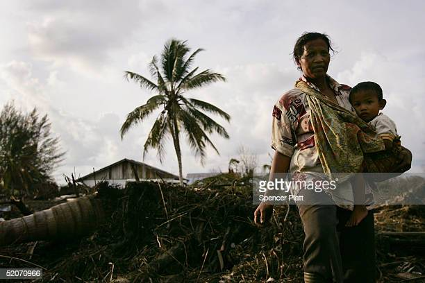 A woman stands among the ruins of her home with her child January 27 2005 in the tsunamiravaged town of Meulaboh Indonesia Over a month since the...