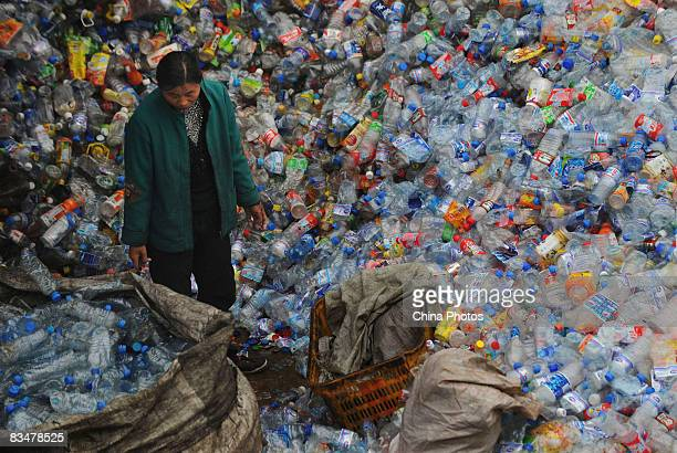 A woman stands amongst a huge pile of used plastic bottles at a plastics recycling mill which is ceasing production as the global financial crisis...