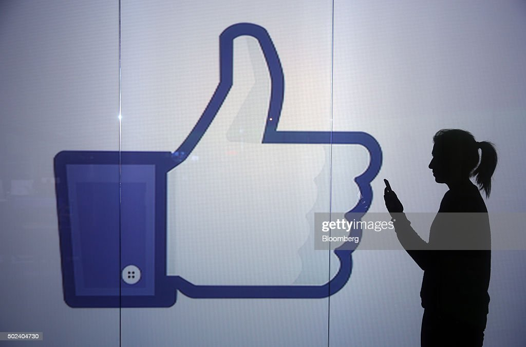 A woman stands and checks her smartphone whilst framed against an illuminated wall bearing Facebook Inc.s 'Thumbs Up' symbol in this arranged photograph in London, U.K., on Wednesday, Dec. 23, 2015. Facebook Inc.s WhatsApp messaging service, with more than 100 million local users, is the most-used app in Brazil, according to an Ibope poll published on Dec. 15. Photographer: Chris Ratcliffe/Bloomberg via Getty Images