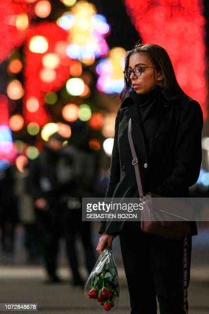 A woman stands and holds flowers on December 13 in tribute to the victims of the attack near the Christmas market of Strasbourg in eastern France on...
