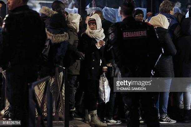 A woman stands as she is evacuated by police officers and gendarmes from a makeshift camp under the Stalingrad railway station in Paris on March 30...