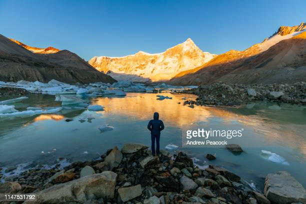 a woman stands at a glacial lake in front of mount san lorenzo east face at dawn - argentina stock pictures, royalty-free photos & images