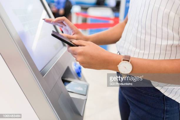 a woman stands at a kiosk in an airport as she gets her luggage tags - kiosk stock pictures, royalty-free photos & images