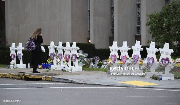 A woman stands at a memorial outside the Tree of Life synagogue after a shooting there left 11 people dead in the Squirrel Hill neighborhood of...