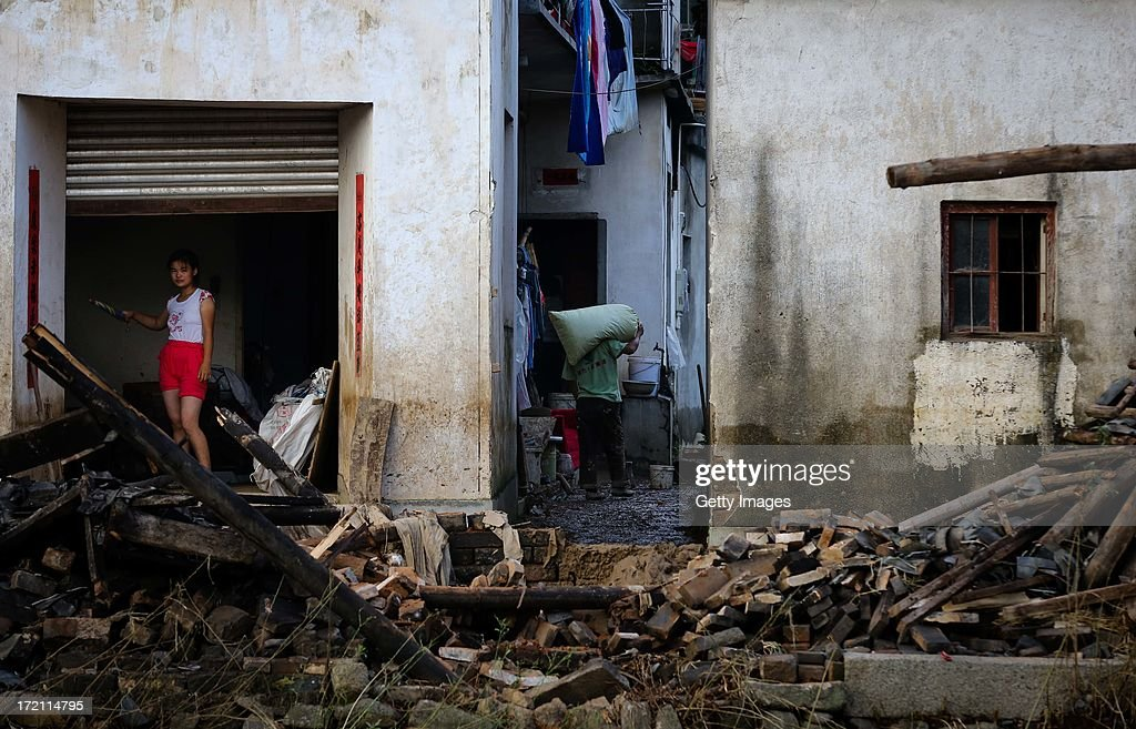 A woman stands at home at Chengkan village after flood waters receded on July 1, 2013 in Huangshan, China. Four people were killed after a torrential rain hit Huangshan on June 30.
