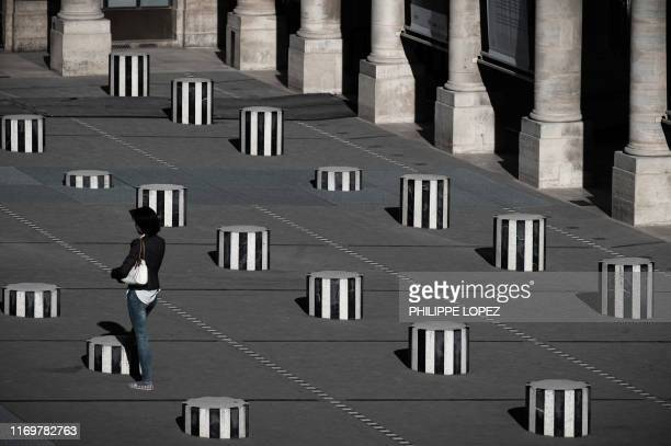 A woman stands at the Colonnes de Buren an art installation by French artist Daniel Buren in the inner courtyard of the Palais Royal gardens in Paris...