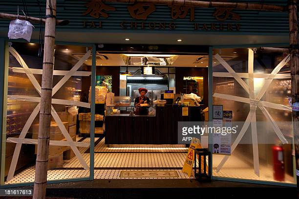 A woman stands at the counter of a bakery which has tape on its windows to protect them from strong winds in the Soho district of Hong Kong on...