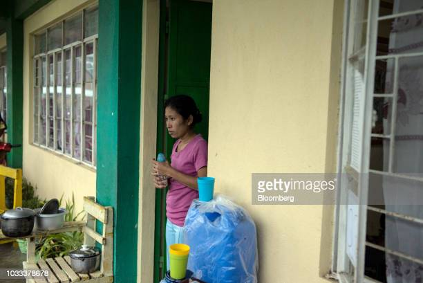 A woman stands at the doorway of a temporary evacuation center at Balzain East Elementary School ahead of Typhoon Mangkhut's arrival in Tuguegarao...