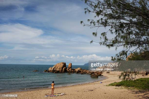 A woman stands at the edge of the water at Horseshoe Bay on April 25 2019 in Bowen Australia Bowen population just over 10 is located on the coast of...